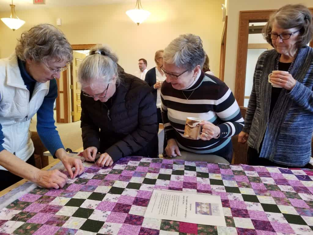 Women working a comforter blanker on February 2020 at Zion Mennonite Church, Broadway VA (Photo by Elwood Yoder)